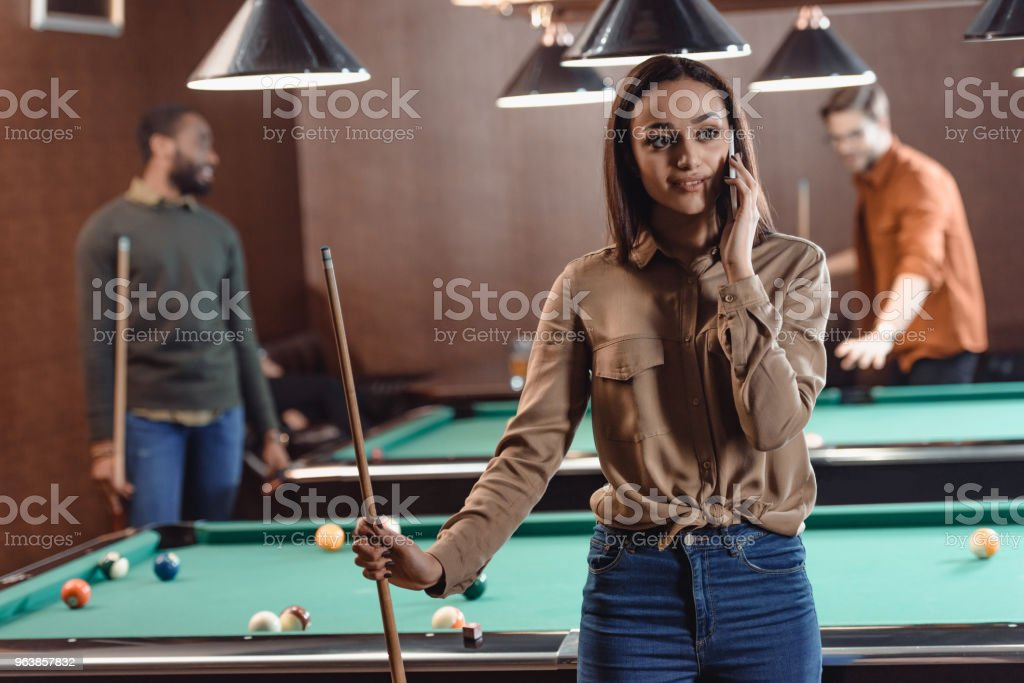 young beautiful woman speaking on smartphone at pool bar - Royalty-free Adult Stock Photo