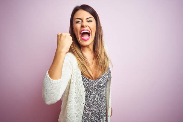 Young beautiful woman standing over pink isolated background angry and mad raising fist frustrated and furious while shouting with anger. Rage and aggressive concept. stock photo