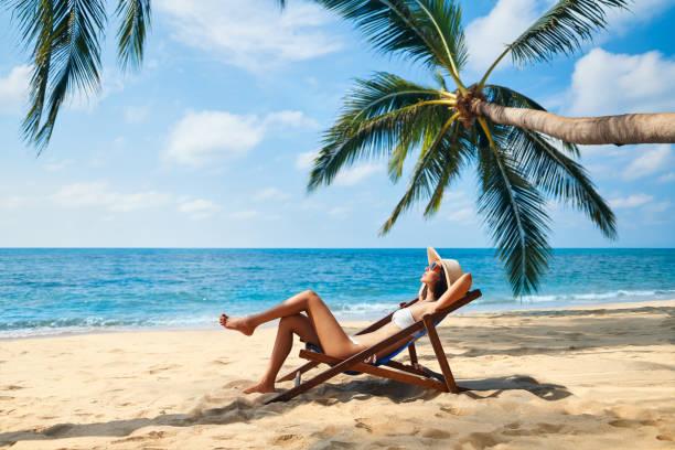 Joven hermosa mujer tomar el sol y relajarse en la playa tropical - foto de stock
