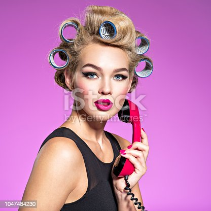Young beautiful woman talking by a red vintage phone. Girl with blue curlers looking sad when calling,