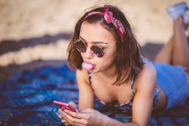 Young beautiful woman texting and blowing a bubble gum stock photo