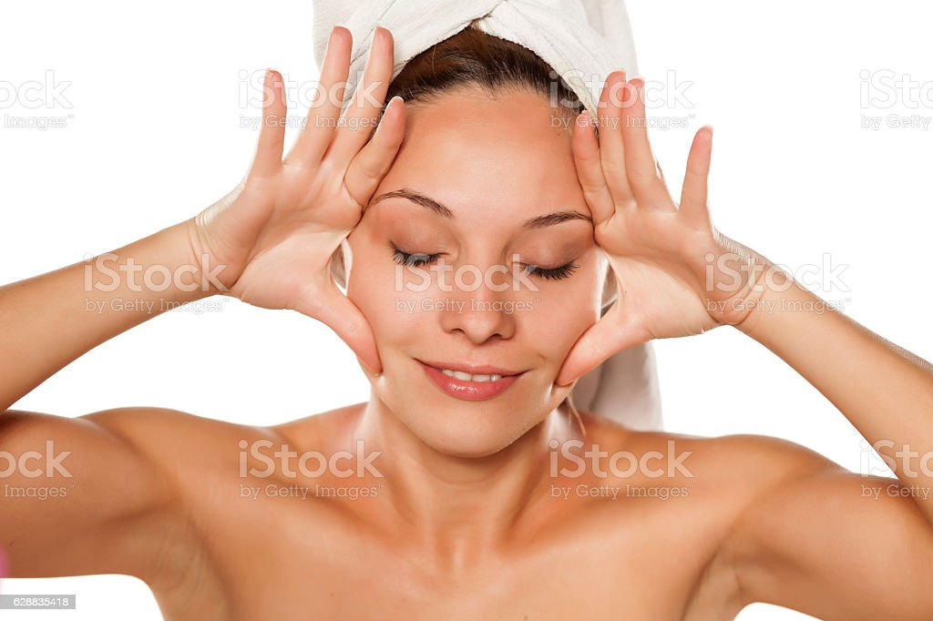 young beautiful woman tightens her face with her hands stock photo