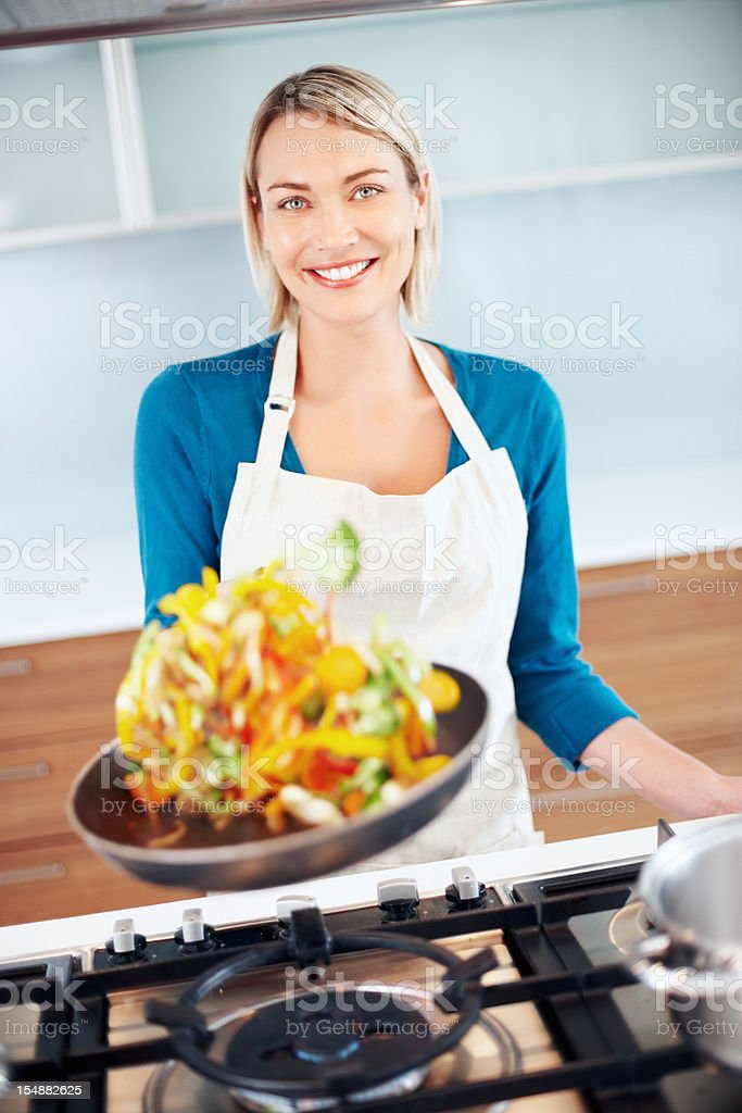 Young beautiful woman tossing food in a frying pan stock photo