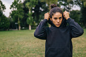 Young adult woman working out in black sweatshirt in a public park