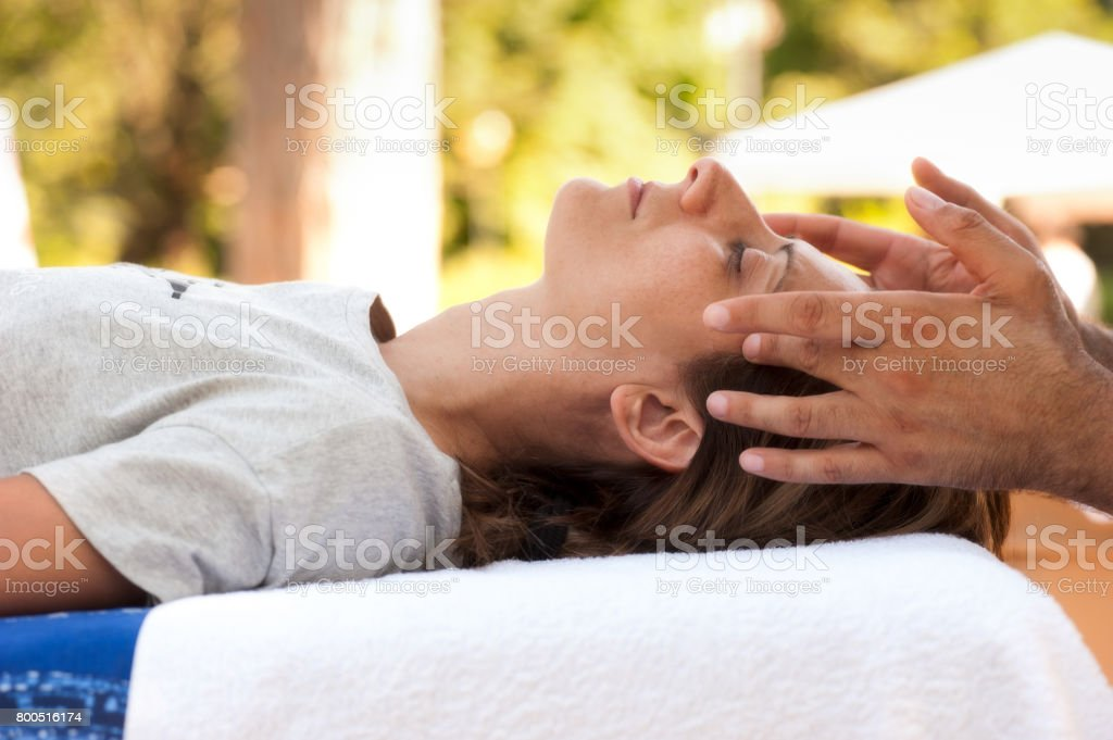 A young beautiful woman undergoes a relaxing facial massage stock photo