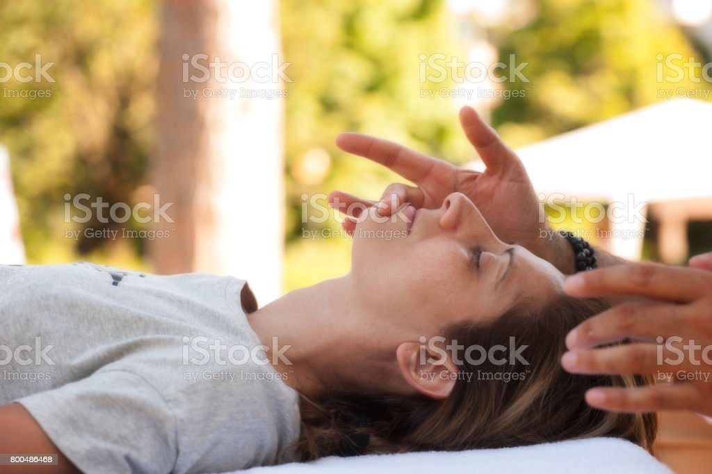 A young beautiful woman undergoes professional relaxing facial massage stock photo