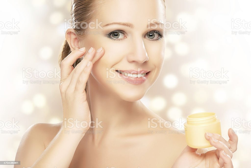 young beautiful woman using a face cream stock photo