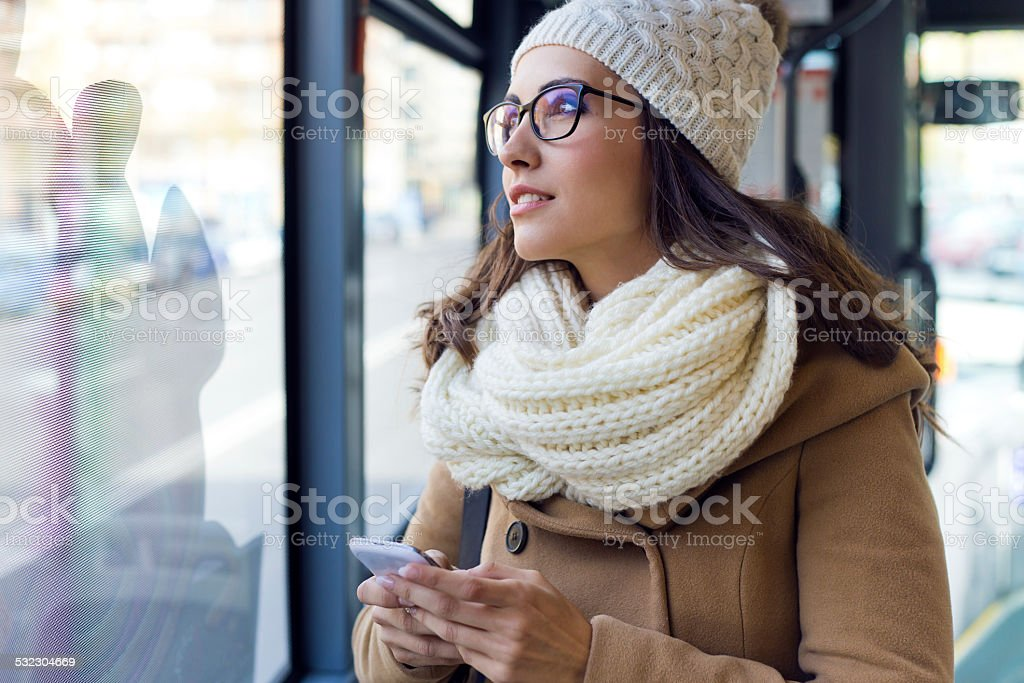 Young beautiful woman using her mobile phone on a  bus. stock photo