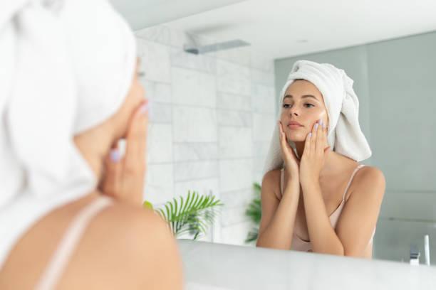 피부 얼굴 크림 로션을 사용하여 젊은 아름다운 여자 - 일과 뉴스 사진 이미지