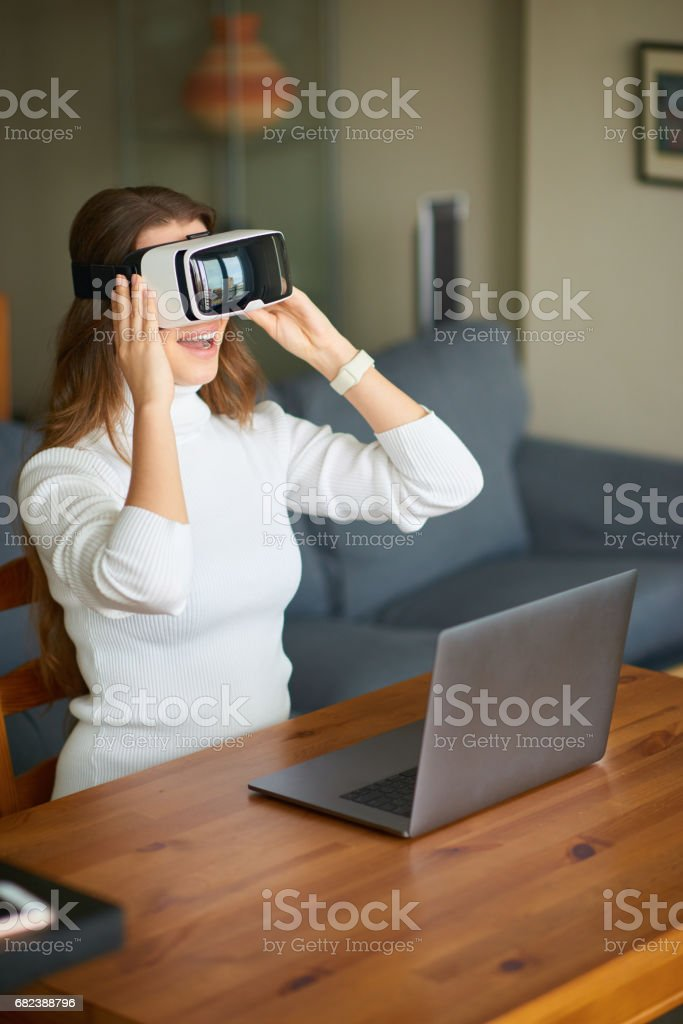 Young beautiful woman using virtual reality headset while working from home foto stock royalty-free