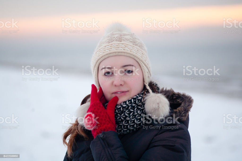 Young beautiful woman walking in a park forest in cold winter air....