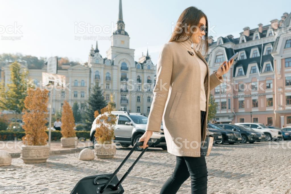 Young beautiful woman walks along city street with travel suitcase...