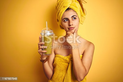 istock Young beautiful woman wearing a towel drinking detox juice over yellow isolated background serious face thinking about question, very confused idea 1167937545
