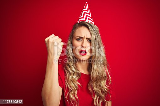 808681534 istock photo Young beautiful woman wearing bitrhday hat over red isolated background annoyed and frustrated shouting with anger, crazy and yelling with raised hand, anger concept 1173840842