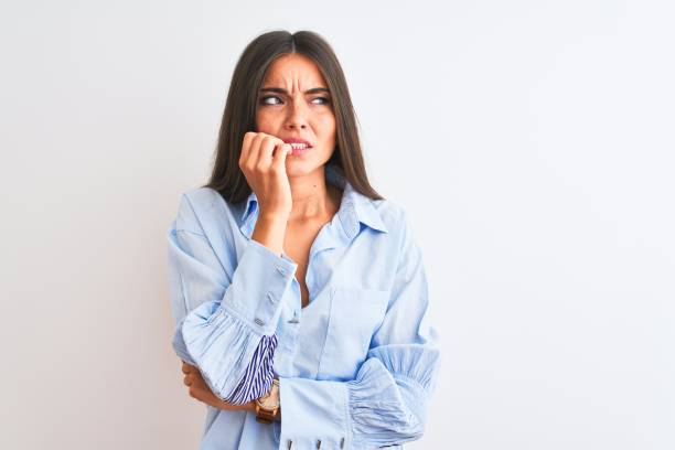 Young beautiful woman wearing blue elegant shirt standing over isolated white background looking stressed and nervous with hands on mouth biting nails. Anxiety problem. stock photo
