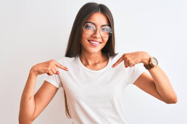 Young beautiful woman wearing casual t-shirt and glasses over isolated white background looking confident with smile on face, pointing oneself with fingers proud and happy. stock photo