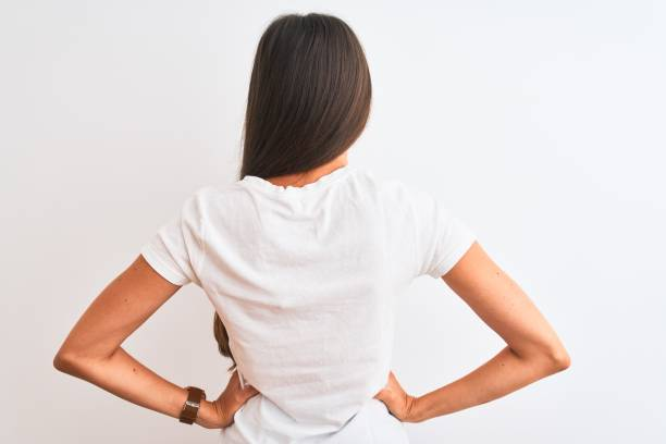 Young beautiful woman wearing casual t-shirt standing over isolated white background standing backwards looking away with arms on body Young beautiful woman wearing casual t-shirt standing over isolated white background standing backwards looking away with arms on body bending over backwards stock pictures, royalty-free photos & images