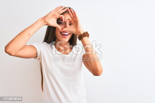 Young beautiful woman wearing casual t-shirt standing over isolated white background Doing heart shape with hand and fingers smiling looking through sign