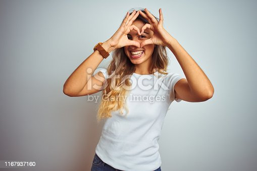 Young beautiful woman wearing casual white t-shirt over isolated background Doing heart shape with hand and fingers smiling looking through sign