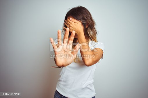 Young beautiful woman wearing casual white t-shirt over isolated background covering eyes with hands and doing stop gesture with sad and fear expression. Embarrassed and negative concept.