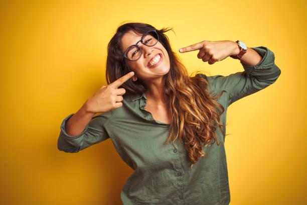 年輕的漂亮女人穿著綠色襯衫和眼鏡在喊低孤立的背景微笑歡快顯示,並指著手指牙齒和嘴。牙齒健康概念。 - 幸福 個照片及圖片檔