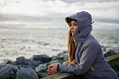 Shoot of young beautiful woman wearing rain jacket in cold weather