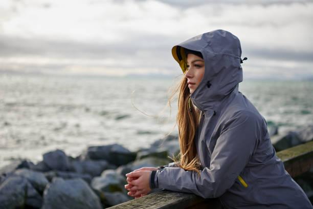 年輕美麗的婦女穿著雨夾克在寒冷的天氣 - 外套 個照片及圖片檔