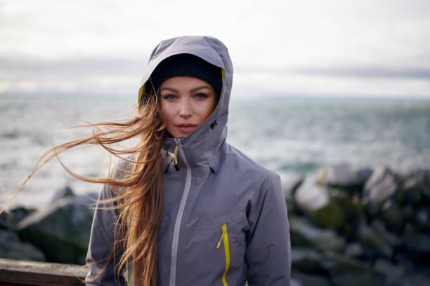 junge schöne frau mit regenjacke bei kaltem wetter - lange jacken stock-fotos und bilder