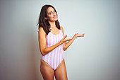Young beautiful woman wearing striped pink swimsuit swimwear over isolated background Inviting to enter smiling natural with open hand