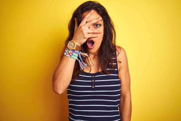 Young beautiful woman wearing striped t-shirt standing over isolated yellow background peeking in shock covering face and eyes with hand, looking through fingers with embarrassed expression. Young beautiful woman wearing striped t-shirt standing over isolated yellow background peeking in shock covering face and eyes with hand, looking through fingers with embarrassed expression. aghast stock pictures, royalty-free photos & images