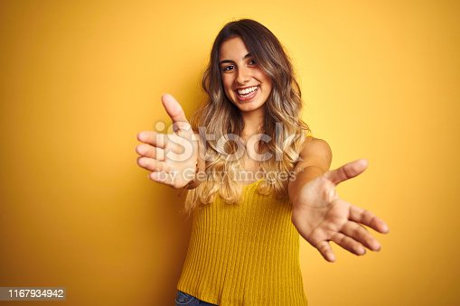 istock Young beautiful woman wearing t-shirt over yellow isolated background looking at the camera smiling with open arms for hug. Cheerful expression embracing happiness. 1167934942