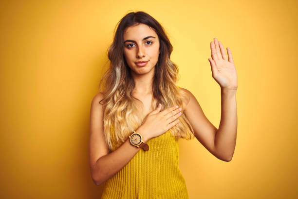 young beautiful woman wearing t-shirt over yellow isolated background swearing with hand on chest and open palm, making a loyalty promise oath - fedeltà foto e immagini stock