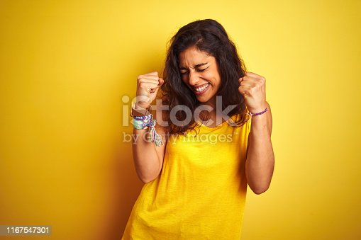 Young beautiful woman wearing t-shirt standing over isolated yellow background very happy and excited doing winner gesture with arms raised, smiling and screaming for success. Celebration concept.