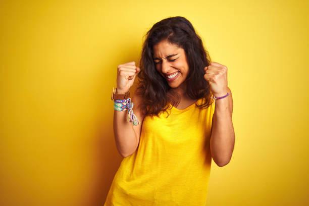 t-shirt desgastando da mulher bonita nova que está sobre o fundo amarelo isolado muito feliz e excitado que faz o gesto do vencedor com os braços levantados, sorrindo e gritando para o sucesso. conceito da celebração. - excitação - fotografias e filmes do acervo