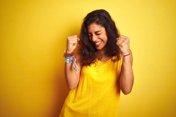 young beautiful woman wearing t-shirt standing over isolated yellow background very happy and excited doing winner gesture with arms raised, smiling and screaming for success. celebration concept. - alegria imagens e fotografias de stock