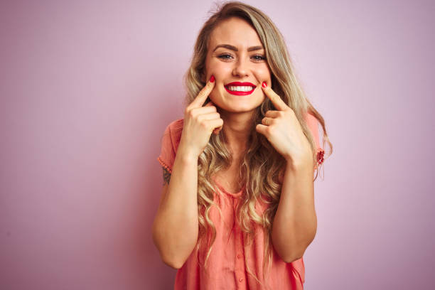young beautiful woman wearing t-shirt standing over pink isolated background smiling with open mouth, fingers pointing and forcing cheerful smile - smile woman open mouth foto e immagini stock