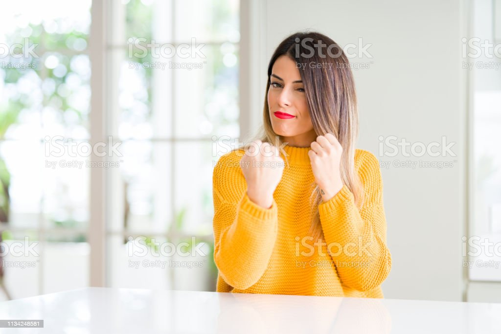 Young beautiful woman wearing winter sweater at home Ready to fight...