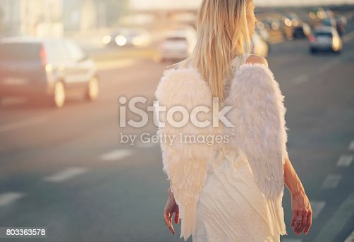 istock Young beautiful woman with angel wings walking near highway, freedom concept 803363578