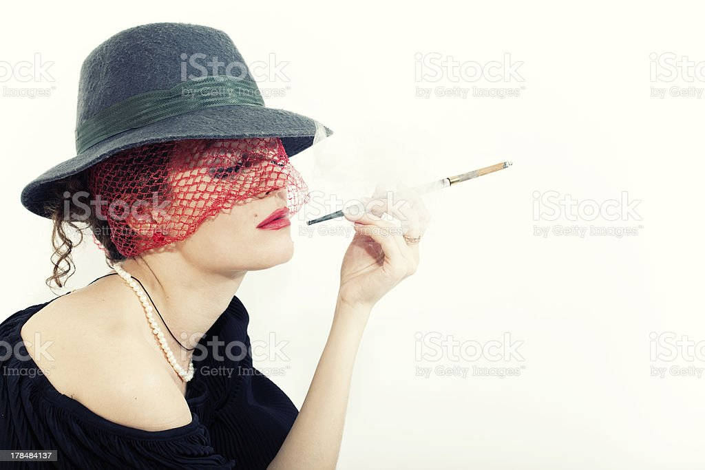 Young beautiful woman with cigarette  in hat stock photo