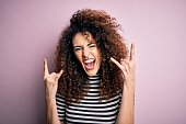 istock Young beautiful woman with curly hair and piercing wearing casual striped t-shirt shouting with crazy expression doing rock symbol with hands up. Music star. Heavy concept. 1213844322