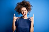 istock Young beautiful woman with curly hair and piercing wearing casual blue t-shirt shouting with crazy expression doing rock symbol with hands up. Music star. Heavy concept. 1213844620