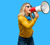 istock Young beautiful woman with headphones communicates shouting loud holding a megaphone, expressing success and positive concept, idea for marketing or sales 1042164724