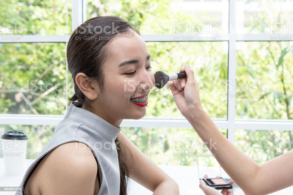 Young beautiful woman with Makeup brush. Friends doing make-upin a coffee shop. royalty-free stock photo