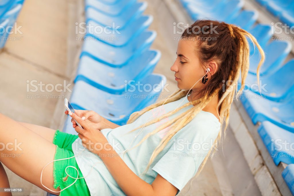 Young beautiful woman with smartphone and earphones stock photo