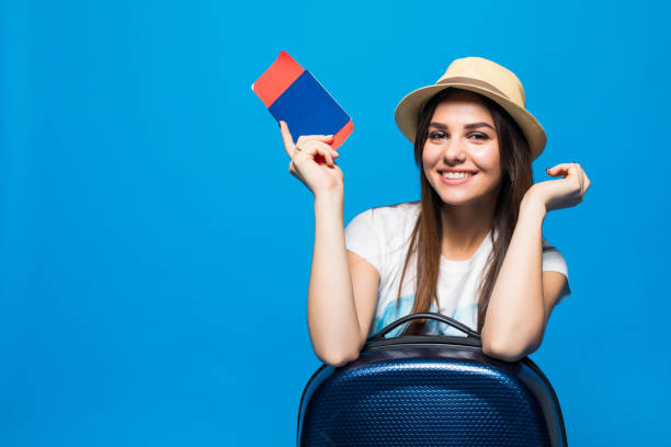 Young beautiful woman with suitcase holding passport on blue picture id867933818?b=1&k=6&m=867933818&s=612x612&w=0&h=pviusmjqupbiw90vyikldeyup4dabgh rfqwrl7kyoq=