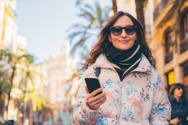 Young beautiful woman with sunglasses and smartphone in her hand walking down the street