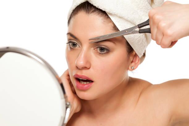 年輕美麗的女人與毛巾在她的頭塑造她的眉毛用剪刀圖像檔