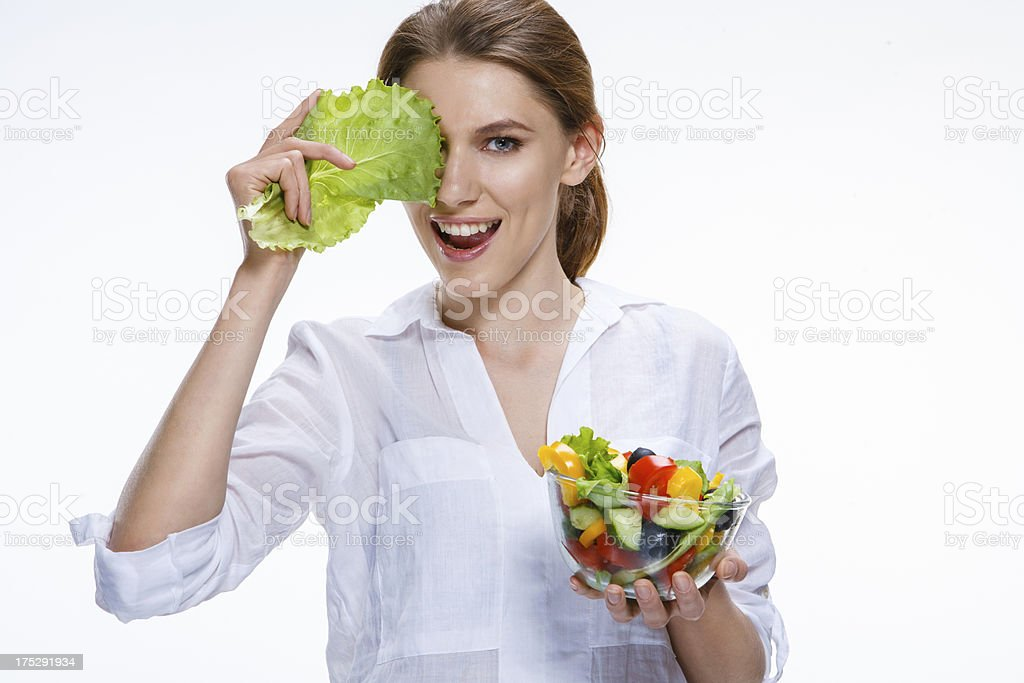 Young beautiful woman with vegetable salad bowl in one hand royalty-free stock photo