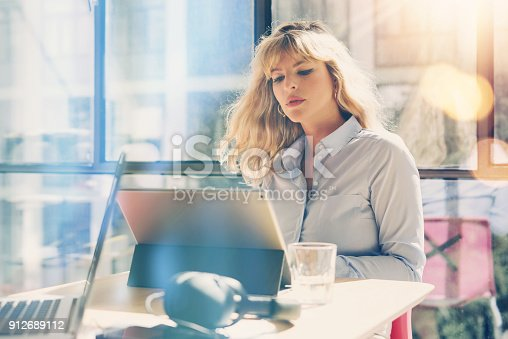 istock Young beautiful woman working at the modern office loft.Coworker using electronic touch tablet computer on workplace.Horizontal. Blurred background. 912689112