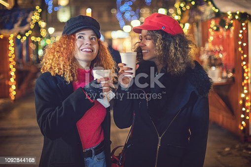 Young beautiful women are shopping hot drinks at Christmas market, on the break during holiday shopping